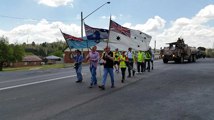 Members of the RSL and Mayor Michael Pearce (centre with the Australian National Flag) head off down the highway to the strains of the Bag Pipes and the applause of the community of Uralla.